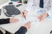 Workteam working on a economic document — Stock Photo