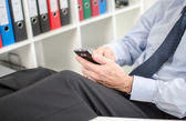 Relaxed businessman using his smartphone — ストック写真