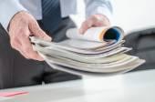 Businessman holding magazines — ストック写真
