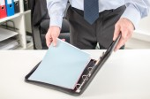 Businessman taking folder from his briefcase — Photo