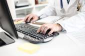 Doctor typing on a computer keyboard — Stock Photo