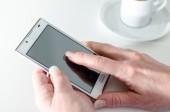 Businesswoman using a smartphone during coffee break — ストック写真