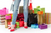 Woman standing before many gifts and shopping bags — Stock Photo