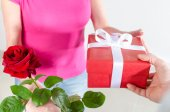 Man giving a rose and a gift to a woman — Stockfoto