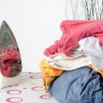Pile of laundry and iron on ironing board — Stock Photo #71044175
