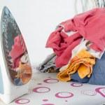 Pile of laundry and iron on ironing board — Stock Photo #71044183