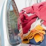 Pile of laundry and iron on ironing board — Stock Photo #71044191