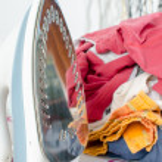 Pile of laundry and iron on ironing board — Stock Photo #71044197