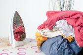 Hög med tvätt och stryka på strykbräda — Stockfoto