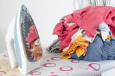 Pile of laundry and iron on ironing board — Stock Photo