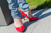 Fashioned woman wearing red high heel shoes — Stock Photo