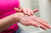 Woman applying cream on her hand — Stock Photo