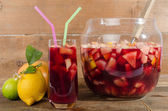 Glass and punch bowl of sangria — Stock Photo