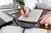 Lekarz pracuje nad dokumentem — Zdjęcie stockowe