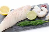 Fresh raw cod fillet on a slate plate — Stock Photo