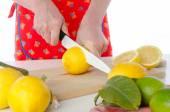 Woman cutting a lemon in half — Stock Photo