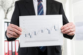 Businessman showing candlestick chart — Stock Photo