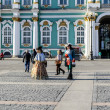 Постер, плакат: Actors in the images of Peter The Great and court lady walks among the tourists on Palace Square on the background of the Hermitage