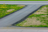 The turn of the airport landing runway road with painted white yellow horizontal signals and lights — Stok fotoğraf