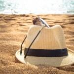 Straw fedora hat on sandy beach — Stock Photo #55183861