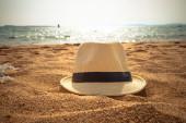 Straw fedora hat on sandy beach — Stock Photo
