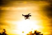 Quadrocopter on sunset sky — Stockfoto