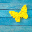 Decorative yellow butterfly on blue wooden background — Stock Photo #52006965