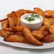 Fried potato wedges with white sauce on white plate — Stock Photo #53188257