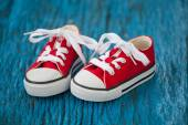 Red baby sneakers on wooden blue background — Zdjęcie stockowe