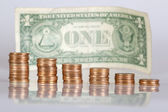 Columns of gold coin in front of one dollar bill — Stock Photo