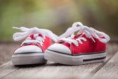 красные детские кроссовки на деревянных фоне — Стоковое фото