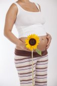 Pregnant woman holding a sunflower — Foto Stock