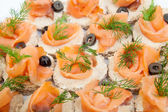 Party platter of bite size smoked salmon appetisers — Stock Photo