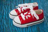 Scarpe da ginnastica bambino rosso su sfondo blu in legno — Foto Stock