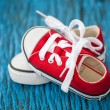 Cute red baby sneakers on blue wooden background — Stock Photo #63902899