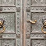 Decorative metal gate ornament. Antique iron door with classic ornaments. lion heads, Door knocker — Stock Photo #69740755