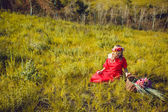 Girl in the red dress is walking On the field — ストック写真
