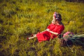 Girl in the red dress is walking On the field — Stock Photo