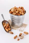 Roasted peanuts in shells over white background — Stock Photo