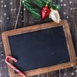 Black board for Christmas message over wooden background — Stock Photo #57778659