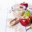 Fresh fruits and rolled oats over white background — Stock Photo #57780449
