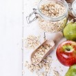Fresh fruits and rolled oats over white background — Stock Photo #61675545