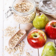 Fresh fruits and rolled oats over white background — Stock Photo #61675987