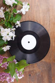 Vinyl record and spring flowers on the table — Stock Photo