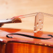 Fragment of a violin on a wooden background — Stock Photo #54813429