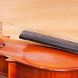 Fragment of a violin on a wooden background — Stock Photo #54813563