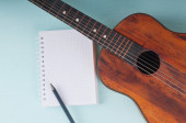 Little guitar and blank notebook with pencil on the azure surfac — Stock Photo