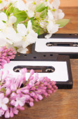 Audio cassette and spring flowers on a wooden table — Stock Photo