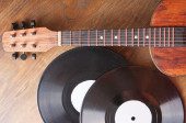 Vintage acoustic guitar and vinyl record on a wooden background — Stockfoto