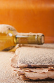 Vintage bottle of wine and a book covered with dust — Stock Photo